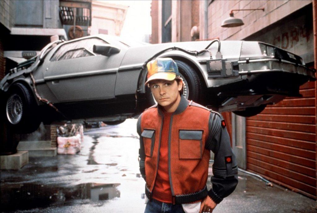 """Michael J. Fox jako Marthy McFly w drugiej części """"Powrotu do przyszłości"""". W tle wehikuł czasu - DeLorean DMC-12"""