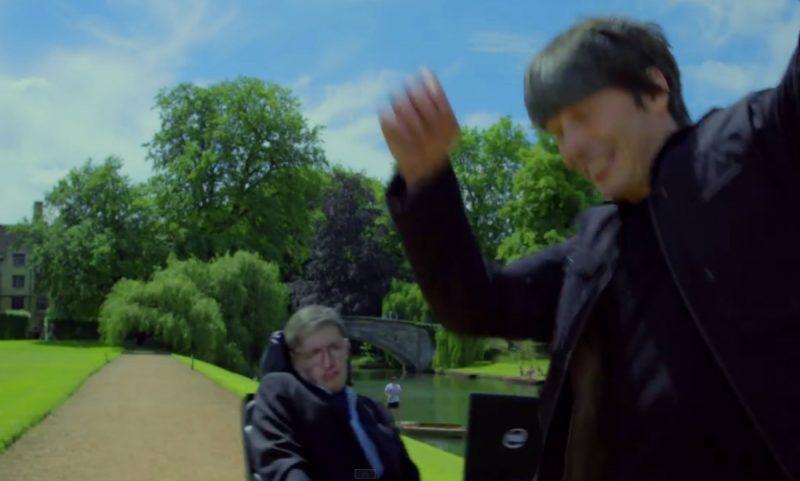 """Stephen Hawking potrąca wózkiem Briana Coxa i odjeżdża, śpiewając """"Galaktyczną Piosenkę"""" Monty Pythona. Fot. Monty Python/YouTube"""