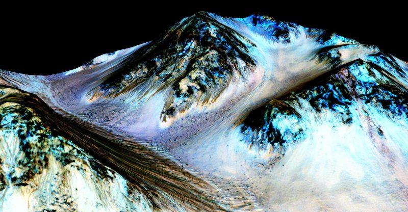 Brązowe smugi to ślady spływającej ma Marsie wody. Obraz powstał z nałożenia zdjęć zrobionych w podczerwieni na przestrzenną mapę Marsa. Kolory nie oddają rzeczywistości, uwydatniają za to skład gruntu. Skala pionowa jest tu powiększona 1,5 raza. Fot. NASA/JPL/University of Arizona