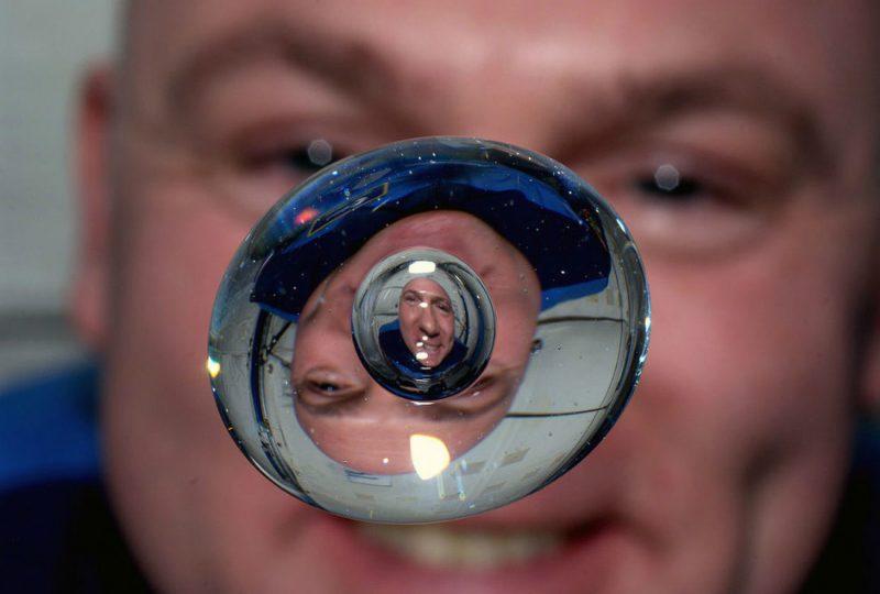 Astronauta Europejskiej Agencji Kosmicznej Andre Kuipers i jego podobizna - załamana i odbita w kropli wody. Fot. NASA
