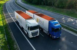 Blue truck overtaking white truck on an asphalt highway between